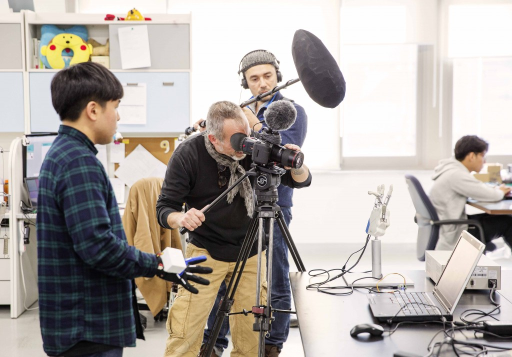 프랑스 다큐멘터리 제작팀이 14일 오후 제1공학관 505B 연구실에서 배준범 교수팀이 개발한 로봇기술을 촬영했다. 사진 속 장면은 이정수 석·박사통합과정 연구원(왼쪽)이 특수장갑으로 로봇손을 제어하는  모습이다.