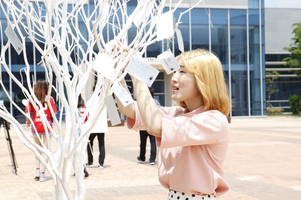이번 축제의 컨셉인 '바람(Wish and Wind)'에 맞춰 마련된 '소원나무'에 UNIST 여학생이 소원 쪽지를 써서 매달고 있다. / 사진 : 스튜디오 인감-박진우
