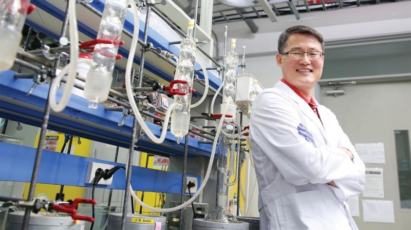 백종범 교수가 실험실에서 반응용기를 배경으로 웃고 있다. 화학합성에서는 이런 용기들을 깨끗이 닦는 게 무척 중요하다. | 사진: 김경채