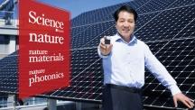 석상일 교수가 UNIST 공학관 옥상에 설치된 실리콘 태양전지 판을 배경으로 서 있다. 그의 손에는 차세대 태양전지의 강력한 후보인 페로브스카이트 태양전지 셀이 들려있다. | 사진: 김경채, 디자인: 박혜지
