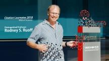 로드니 루오프 UNIST 특훈교수가 UNIST 캠퍼스에 자리한 IBS 다차원 탄소재료 연구단 푯말 앞에서 기념 사진을 촬영했다_배경으로 보이는 건 다양한 탄소 물질의 원자 모형. | 사진: 김경채