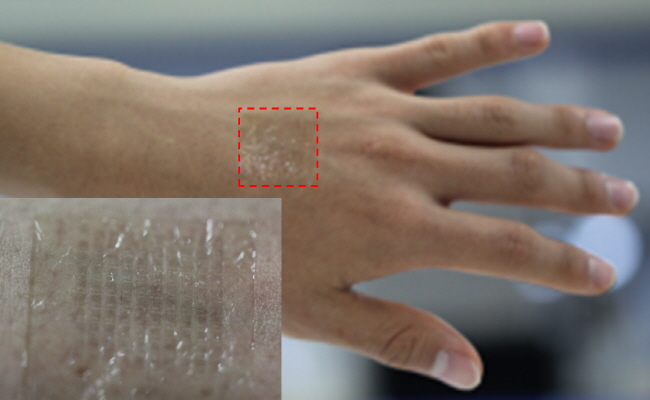 Above image shows a photograph of the transparent wireless sensor attached to the human skin.