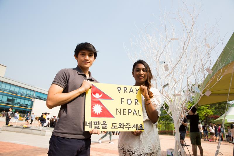 "Luc Loja (left) and Cerian Vaidya (right) of the UNIST International Student Organization (UISO), holding a sign that said ""Pray for Nepal"" on Saturday near the Student Union Building to raise funds to support the victims and send aid to Nepal."
