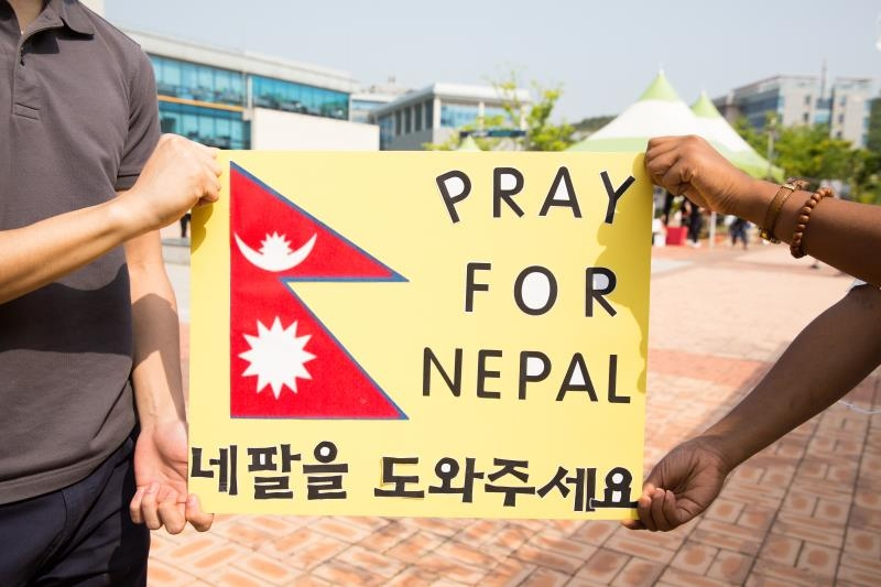 "Members of the UNIST International Student Organization (UISO), holding a sign that said ""Pray for Nepal"" on Saturday near the Student Union Building to raise funds to support the victims and send aid to Nepal."