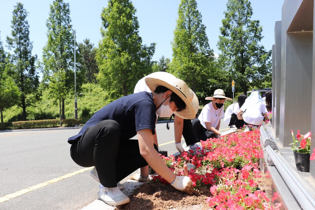 Participants generously donated their time to plant flowers in designated landscaping beds across campus, including theaccess road to UNIST near the symbolic landmark of UNIST. l Image Credit: UNIST Leadership Center